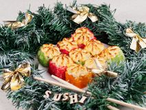 Christmas sushi. New Year sushi. Sushi and Christmas wreath. The word SUSHI from wooden beeches royalty free stock photography