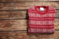 Christmas sweater with pattern and space for text on wooden background. Top view royalty free stock image