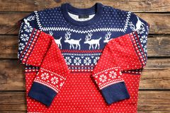 Christmas sweater with pattern on wooden background. Top view royalty free stock photos