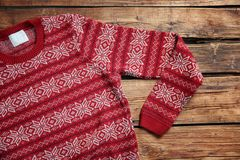 Christmas sweater with pattern. On wooden background, top view stock photo