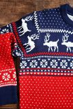 Christmas sweater with pattern. On wooden background, top view royalty free stock image