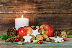 Christmas star cookies, red apples, nuts and spices with festive burning candle Royalty Free Stock Photo