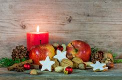 Christmas star cookies, red apples, nuts and spices with festive burning candle Royalty Free Stock Images