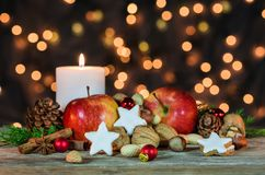 Christmas star cookies, red apples, nuts and spices with festive burning candle Stock Images