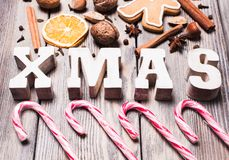 Christmas sweeties. Gingerbreads with spices on the wooden table, wooden letters XMAS and Santa staffs candies. Christmas aroma decor Royalty Free Stock Image