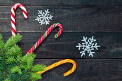 Christmas sweets: bright colored candies in the form of a cane, fir tree and snowflakes on a dark wooden background. Stock Image