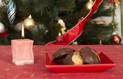 Christmas sweets and candle on the table Stock Photo