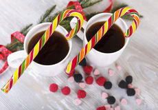 Christmas sweets and coffee. Christmas coffee, sugar cane, spruce twig on a gray background Stock Image