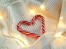 Christmas sweets on female knitting sweater and shiny garland stock photo