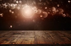 Christmas symbols and bokeh with wooden table. Golden christmas symbols with radiant bokeh on night sky and empty wooden table for decorations royalty free illustration