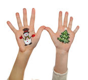 Christmas symbols painted on hands. Christmas tree and Snow man Royalty Free Stock Photos