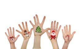 Christmas symbols painted on kid's hands. Santa, snowman, Christmas tree, present box Royalty Free Stock Photography