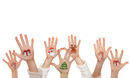 Christmas symbols painted on kid's hands. Santa, snowman, Christmas tree, present box Royalty Free Stock Images