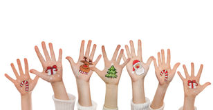 Christmas symbols painted on kid's hands. Santa, snowman, Christmas tree, present box Royalty Free Stock Photo