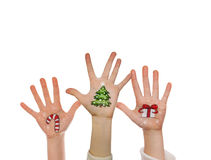 Christmas symbols painted on kid's hands. Santa, snowman, Christmas tree, present box Stock Photos