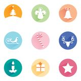 Christmas symbols set: tree, angel, gift, star, candle, bell, sleight, reindeer, candle bar,. White flat design Christmas rounded shape icon set: Christmas tree Royalty Free Stock Images