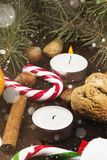 Christmas symbols - stocking, candles, fir-tree, candy cane, cin. Namon, filbert on a dark wooden background. Toned Stock Photo
