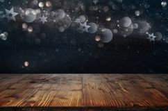 Christmas symbols and wooden table. Silver christmas symbols on night sky and empty wooden table for decorations stock illustration