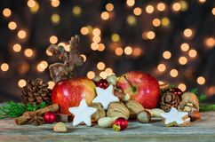 Christmas decoration with candle light, star cookies, red apples, nuts and spices Stock Image