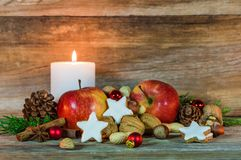 Christmas decoration with candle light, star cookies, red apples, nuts and spices Stock Photography