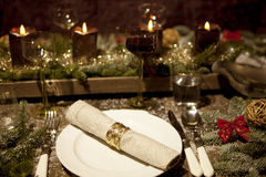 Christmas table, with candles. Christmas place setting with candles, are wine glasses on the table, pine tree branches are adorned with decorative snow Stock Images