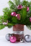 Christmas centerpiece with pink and silver baubles in brown vase. Christmas table centerpiece with fir branches, pink and silver baubles in brown vase on the Royalty Free Stock Photos