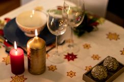 Christmas table with crockery, candles and decoration on tablecloth. Christmas table with crockery, colored candles and decoration on tablecloth stock images