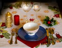 Christmas table with crockery, candles and decoration on tablecloth. Christmas table with crockery, golden and red candles and decoration on tablecloth stock photography