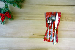 Christmas table, cutlery on a napkin, a sprig of fir with toys. Christmas background: oaks table, plate and cutlery on a napkin, a sprig of fir with toys Royalty Free Stock Photography