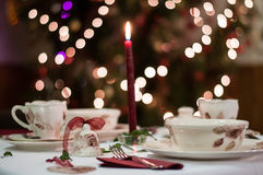Christmas table dacoration. Decorated christmas table with bell and dishes. Bokeh background Royalty Free Stock Photos