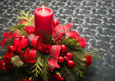 Christmas Table Decoration. A lighted candle Christmas table decoration with red carnations and red ribbons, set on a gray table cloth Royalty Free Stock Image