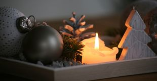 Christmas table decoration for advent and cosy afrernoons. Christmas balls, a wooden Christmas tree and lighted candles produce a cosy and relaxing atmosphere in stock photography