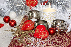 Christmas table decoration. With candle hearts ornament bauble pearls moody Stock Photos