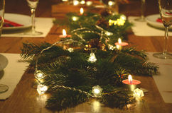 Christmas table decoration with fir tree twigs and electric garland lights on Stock Photo