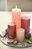 Christmas table decoration with four pink candles and dried fruits scattered Royalty Free Stock Image