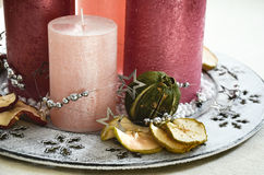 Christmas table decoration with four pink candles and dried fruits scattered Stock Image