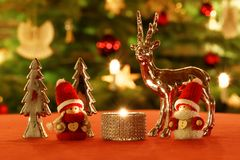 Christmas Table Decoration in Front of Christmas Tree. Christmassy table decoration with silver decoration deer, Christmas trees, tea-candle and dolls in front royalty free stock photo