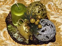 Christmas table decoration on golden colour tablecloth. New year decoration. Christmas table decoration. Two balls silver and golden and a green candle on stock photography