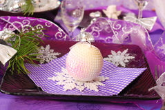 Christmas table decoration in purple  color. Glamour christmas table decoration in purple color with shining ball and snowflakes on glass plate Stock Photos