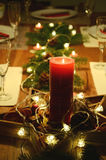 Christmas table decoration with red candle, fir tree twigs and electric garland Royalty Free Stock Images