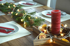 Christmas table decoraton with a red candle, fir tree twigs and electric garland Stock Images