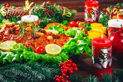 Christmas table dinner time with roasted meats, candles and New Year décor. Background thanksgiving day. Royalty Free Stock Image