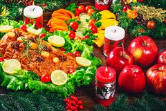 Christmas table dinner time with roasted meats, candles and New Year décor. Background thanksgiving day. Stock Photo