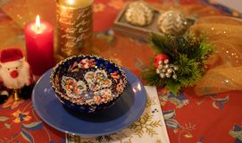 Christmas table with dishes, candles and figure of santa claus stock image