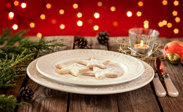 Christmas table - elegant white plate with cookies, red background. Christmas table - elegant white plate with cookies, natural pine tree branch and pinecones on Stock Photography