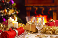 Christmas table with fireplace and Christmas tree. A romantic Christmas dinner table setting with candles and Christmas decorations. A fire is burning in the Royalty Free Stock Photos
