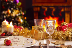 Christmas table with fireplace and Christmas tree. A romantic Christmas dinner table setting with candles and Christmas decorations. On the plate a note with the Royalty Free Stock Images