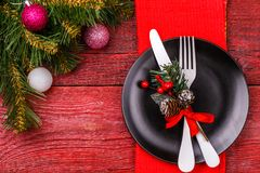 Christmas table with fork and knife on plate and red napkin. Image of Christmas table with fork and knife on plate and red napkin, spruce branches, festive balls Royalty Free Stock Image