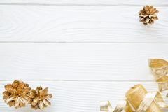 Christmas table, golden cones, candle and ribons, space for text. Christmas background, golden pine cones and golden ribbons on white table, space for text, copy stock image