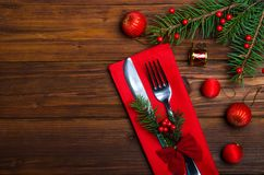 Christmas table: knife and fork, napkin and Christmas tree branch on a wooden table top view with copy space. New Year& x27;s decor of the festive table stock photos